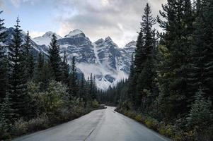 Driving on road in pine forest with rocky mountains in Moraine lake photo