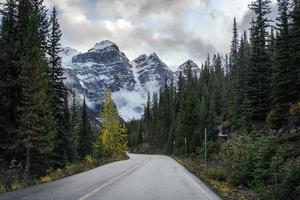 Driving on road in pine forest with rocky mountains at Moraine lake photo