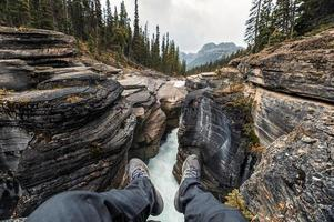 Traveler hanging legs on Mistaya Canyon in Icefields Parkway photo