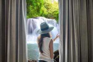 Woman open curtain to view beautiful waterfall flowing natural photo