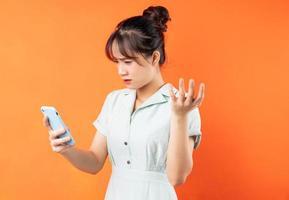 Retrato de niña usando el teléfono y sintiéndose molesto, aislado sobre fondo naranja foto
