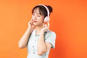 Retrato de niña escuchando música y relajándose, aislado sobre fondo naranja foto