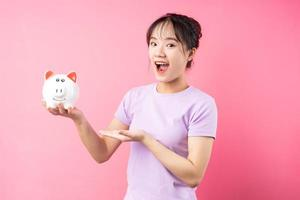 Portrait of girl holding piggy bank in hand, isolated on pink background photo