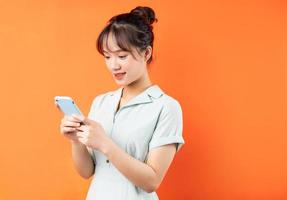 Retrato de niña con teléfono para escuchar música, aislado sobre fondo naranja foto