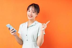 Retrato de niña con teléfono y apuntando hacia la derecha, aislado sobre fondo naranja foto