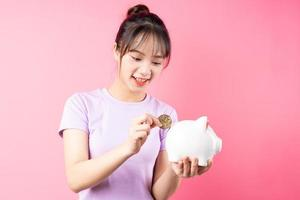 Portrait of girl minting money in pig, isolated on pink background photo