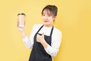 Portrait of cheerful waitress on yellow background photo