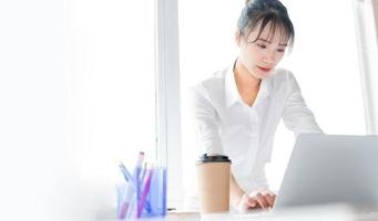 Portrait of young business woman standing and working together with laptop photo