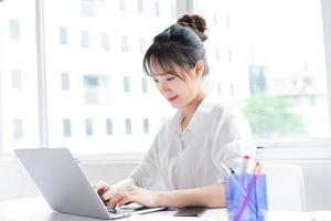Portrait of happy and working young businesswoman photo
