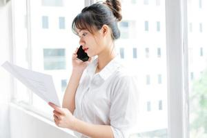 Portrait of young businesswoman standing by the window and making phone calls with her partner photo