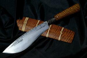 Cuchillo personalizado o enep en la vaina de madera natural sobre fondo de mesa antiguo hecho a mano de Tailandia foto