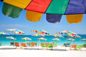 Silla de playa bajo la sombrilla de colorido en la playa de Phuket, Tailandia foto