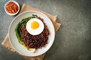 fideos instantáneos secos coreanos con salsa negra picante con huevo frito y kimchi foto