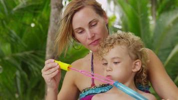 mamma och son leker med bubblor. sköt på röd epik för högkvalitativ 4k, uhd, ultrahd -upplösning. video
