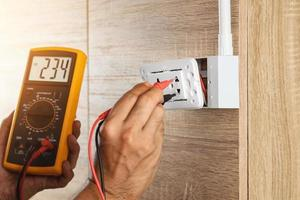 Electrician using a digital meter to measure the voltage at a wall socket on a wooden wall. photo