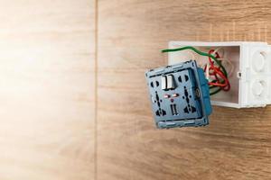 Enchufe de alimentación de CA de tomacorriente de pared universal con puerto USB en una caja de plástico en una pared de madera. foto