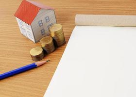 Coins stack with blue pencil and paper house and notepaad photo