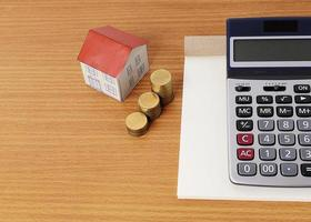 Calculator with notepad and paper house with coins stack photo