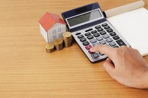 Calculating with Coins stack and paper house and notepad photo