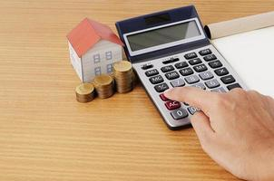 Hand on calculator with coins stack and paper house for mortgage loans concept photo