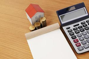 Notepad with Coins stack and paper house with calculator on wooden table desk photo