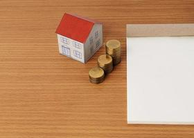 Mortgage loans concept with paper house with coins stack and notepad photo