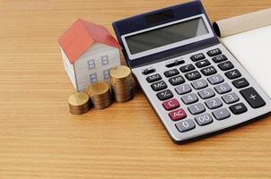 concepto de préstamos hipotecarios con calculadora y pila de monedas y casa de papel foto