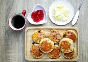 Scone homemade with with strawberry jam and butter. Traditional English backgrounds above photo