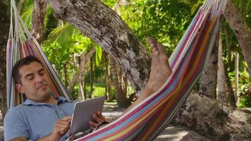 man sitter i hängmatta med digital surfplatta, costa rica. sköt på röd epik för högkvalitativ 4k, uhd, ultrahd -upplösning. video