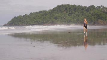 mujer corriendo en la playa, costa rica. filmado en rojo épico para una resolución de alta calidad de 4k, uhd, ultra hd. video