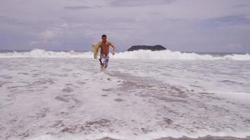 surfista corriendo desde el océano, cámara lenta. filmado en rojo épico para una resolución de alta calidad de 4k, uhd, ultra hd. video