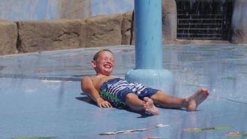 niño acostado y salpicado en la fuente el día de verano, cámara lenta video