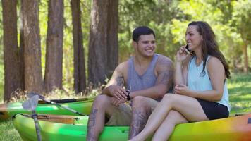 coppia con kayak che parla al cellulare video