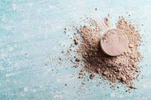 Top view whey protein scoop on blue background, copy space photo