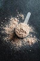 Polvo de proteína en la cuchara de plástico dosificadora sobre fondo oscuro foto