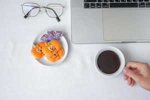 Hand holding coffee cup and eating Halloween Cookies during using computer laptop. Happy Halloween, online shopping, Hello October, fall autumn, Festive, party and holiday concept photo