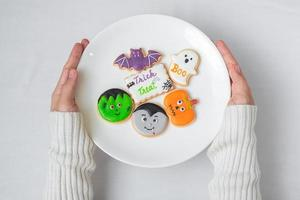 woman hand holding plate of funny Halloween Cookies. Happy Halloween day, Trick or Threat, Hello October, fall autumn, Traditional, party and holiday concept photo