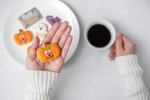 woman hand holding funny Halloween Cookie during drinking coffee. Happy Halloween day, Trick or Threat, Hello October, fall autumn, Traditional, party and holiday concept photo