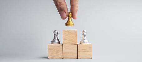 hand holding top of golden chess pawn pieces or leader businessman. victory, leadership, business success, team, recruiting, and teamwork concept photo