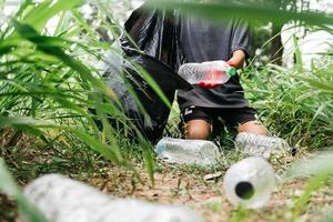 La mano del hombre del muchacho recoge la botella plástica en el bosque. concepto de medio ambiente. foto