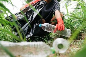 Boy man hand pick up plastic bottle in forest. Environment concept. photo