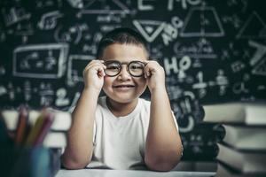 Boy studying and holding glasses leg in classroom. photo