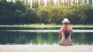 mujer joven sentada en el muelle y mirando el río. foto