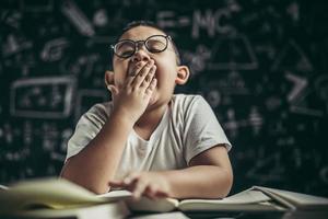 un niño con gafas estudiando y somnoliento. foto