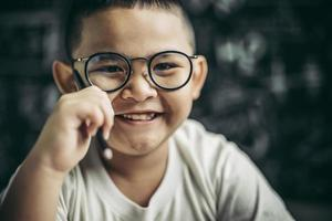 A boy with glasses sitting in the classroom studying photo