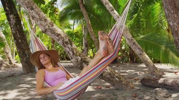 kvinna som sitter i hängmatta med digital surfplatta, costa rica. sköt på röd epik för högkvalitativ 4k, uhd, ultrahd -upplösning. video