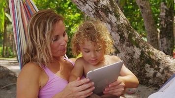 Mother and son in hammock using digital tablet, Costa Rica. Shot on RED EPIC for high quality 4K, UHD, Ultra HD resolution. video