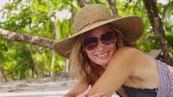 porträtt av kvinna i solglasögon om på tropisk strand. sköt på röd epik för högkvalitativ 4k, uhd, ultrahd -upplösning. video