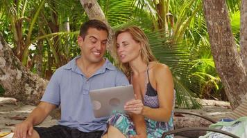 Couple at beach using digital tablet. Shot on RED EPIC for high quality 4K, UHD, Ultra HD resolution. video