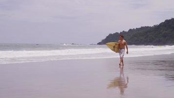 hombre con tabla de surf caminando en la playa. filmado en rojo épico para una resolución de alta calidad de 4k, uhd, ultra hd. video